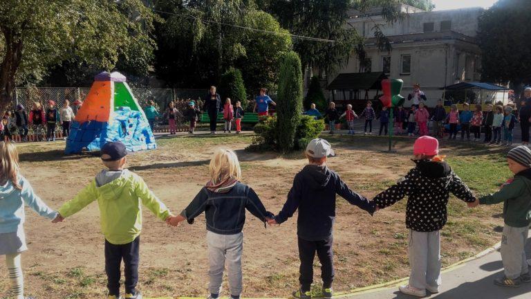Przedszkolaki stoją wogrodzie wkole trzymając się zaręce