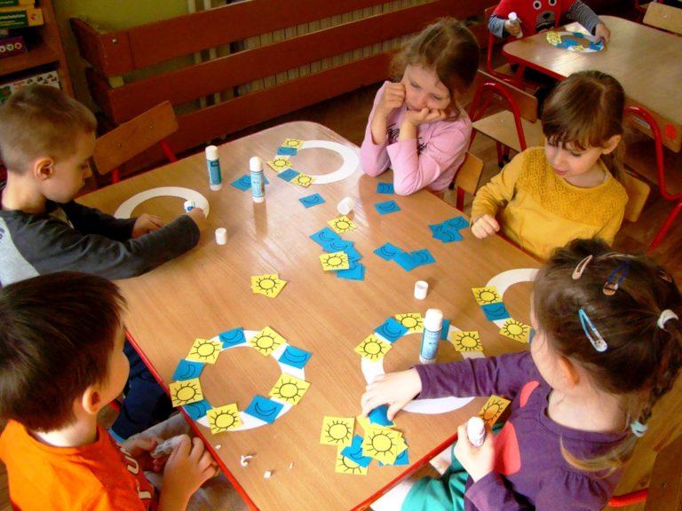 Dzieci układają kolorowe obrazki przy stole