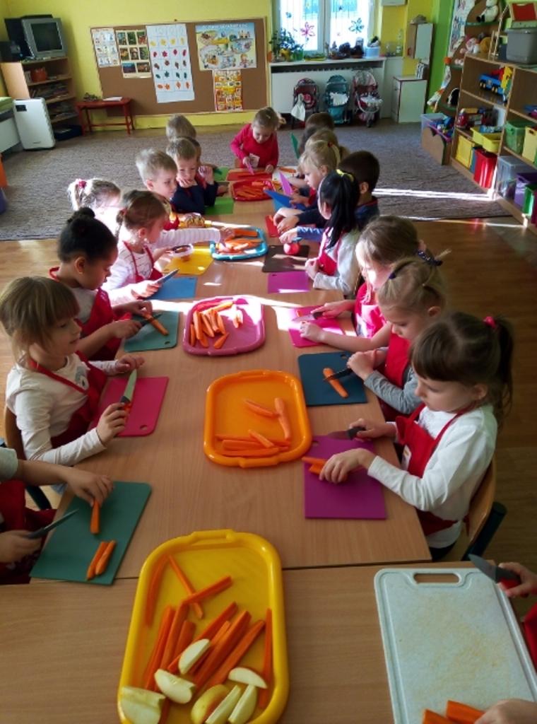 dzieci przygotowują warzywa nasałatkę
