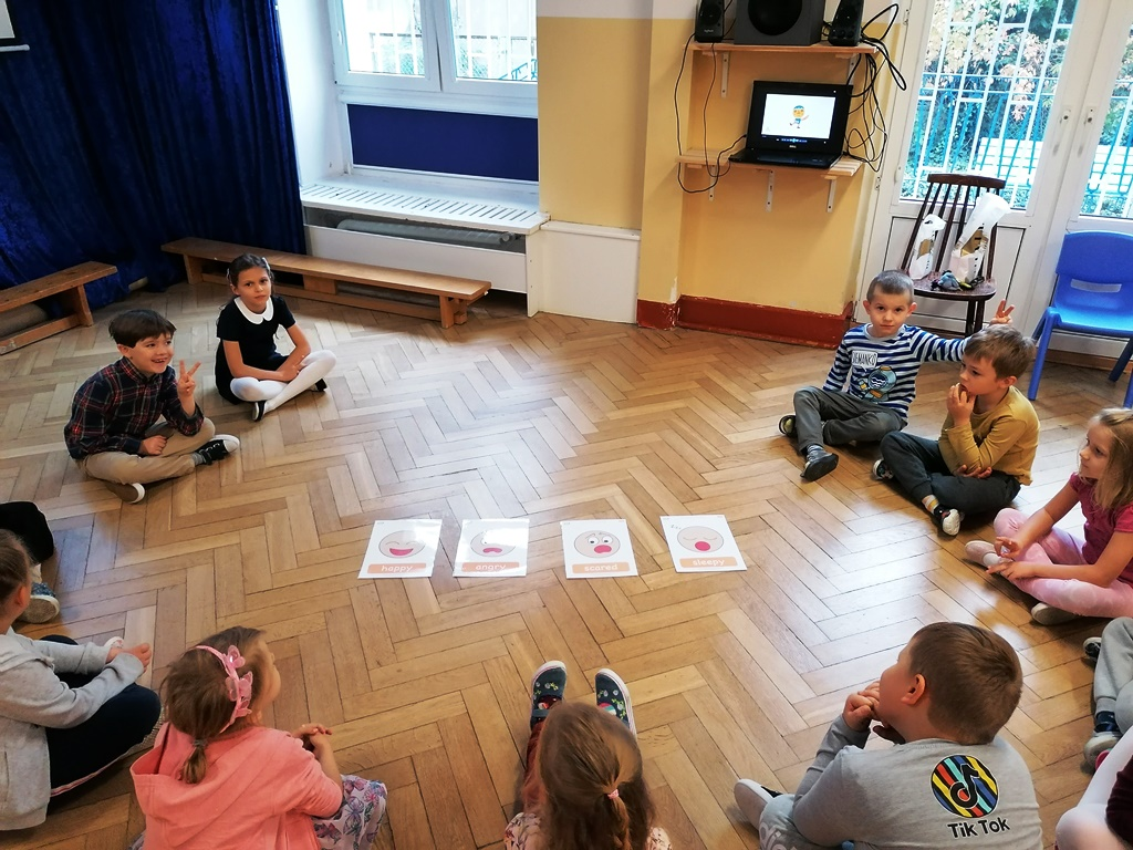 dzieci siedzą wkole napodłodze ioglądają obrazki