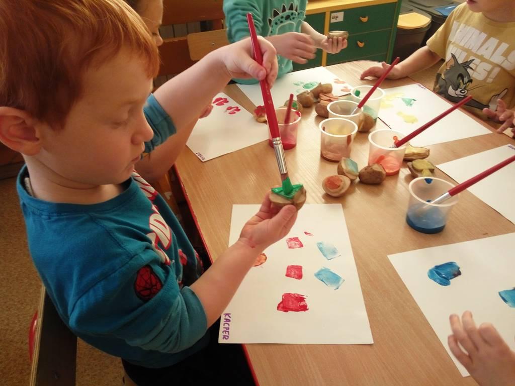chłopiec maluje pędzlem stempelek zziemniaka