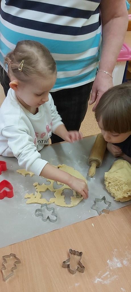 dziewczynka wycina foremkami ciasteczka