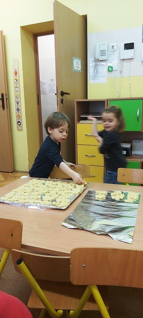 chłopiec układa nablaszce ciastka doupieczenia