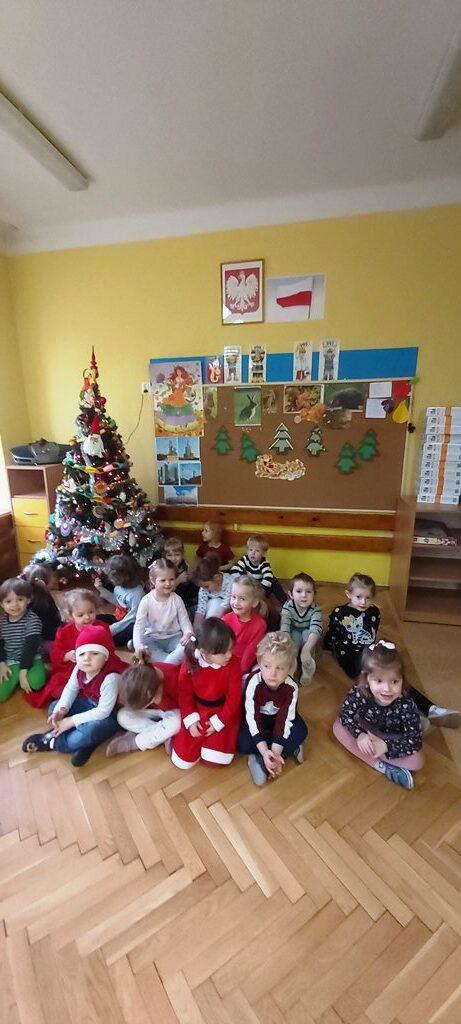 grupa dzieci siedzi przedpięknie udekorowaną choinką