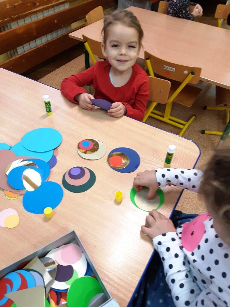 dziewczynki sklejają zkolorowego papieru pawie oczka
