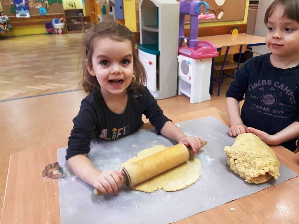 uśmiechnięta dziewczynka wałkuje ciasto naciastka