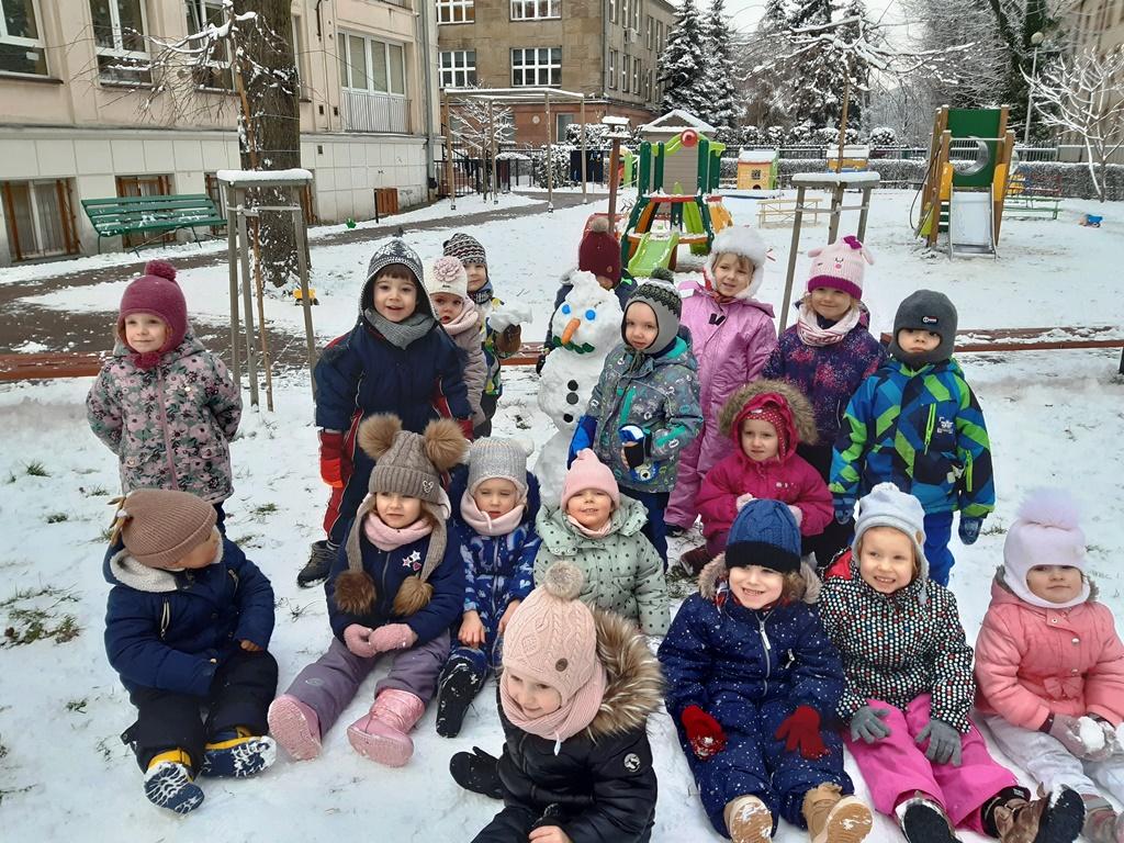 grupa dzieci wzimowych kombinezonach stoją wokół bałwanka