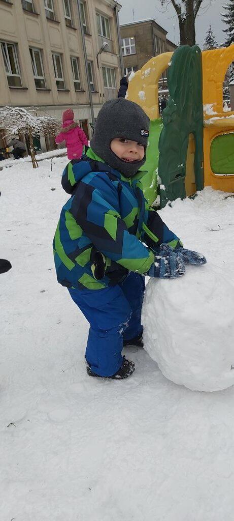 uśmiechnięty chłopiec jest dumny zeswojej dużej kuli śniegowej