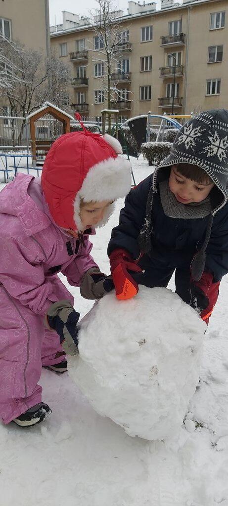 chłopiec zdziewczynką bardzo przejęci toczą kulę śniegową