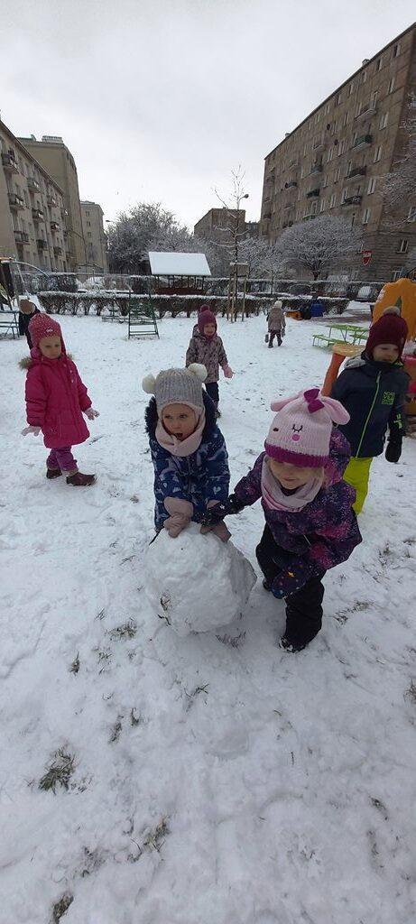 dwie dziewczynki toczą kulę śniegową