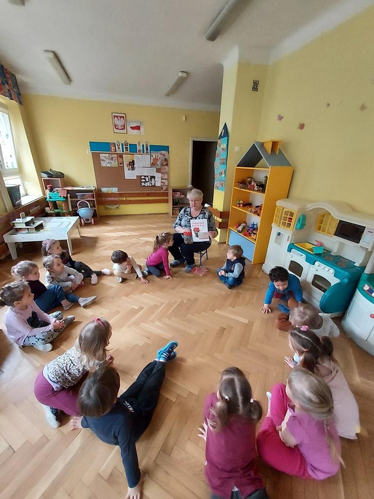 dzieci siedzące wkole napodłodze słuchają nauczycielki, którapokazuje plakat promujący akcję Gorączka złota PCK