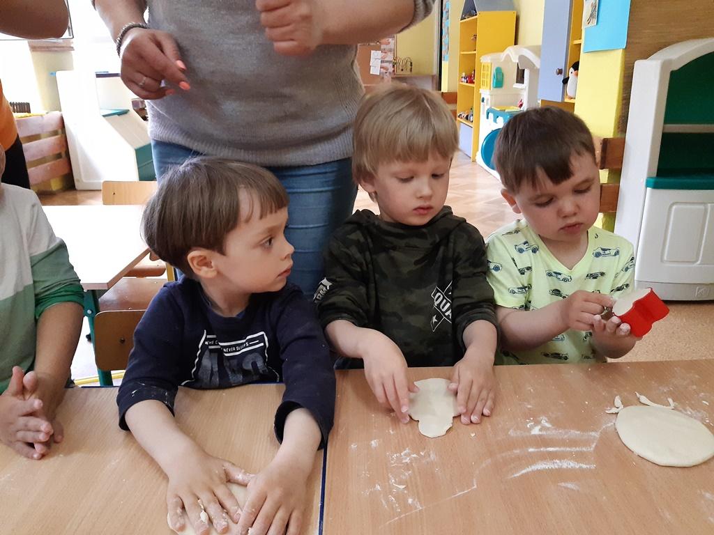 chłopiec smaruje klejem elementy zpapieru potrzebne dowykonania motylka