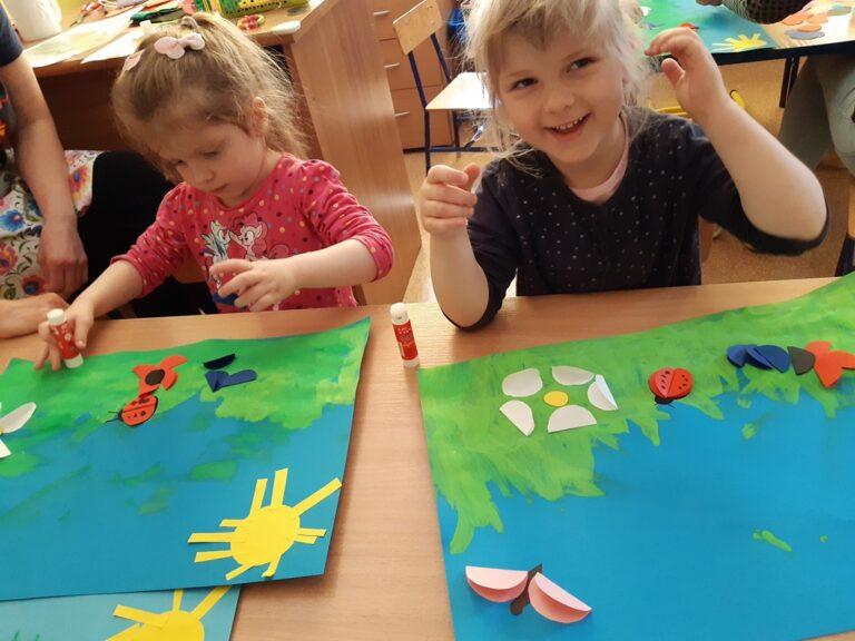 """dwie dziewczynki naklejają elementy kwiatów naobrazku """"Łąka"""""""