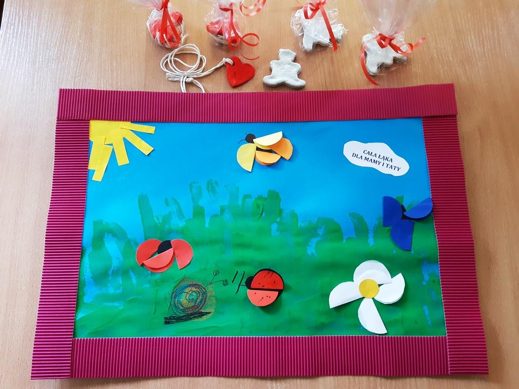 wiosenny obrazek dla rodziców wróżowej ramce (nałące wykonane zpapierowych kół motyl, biedronka, słońce orazkwiaty. Obok leżą serduszko imiś ulepione zmasy solnej)