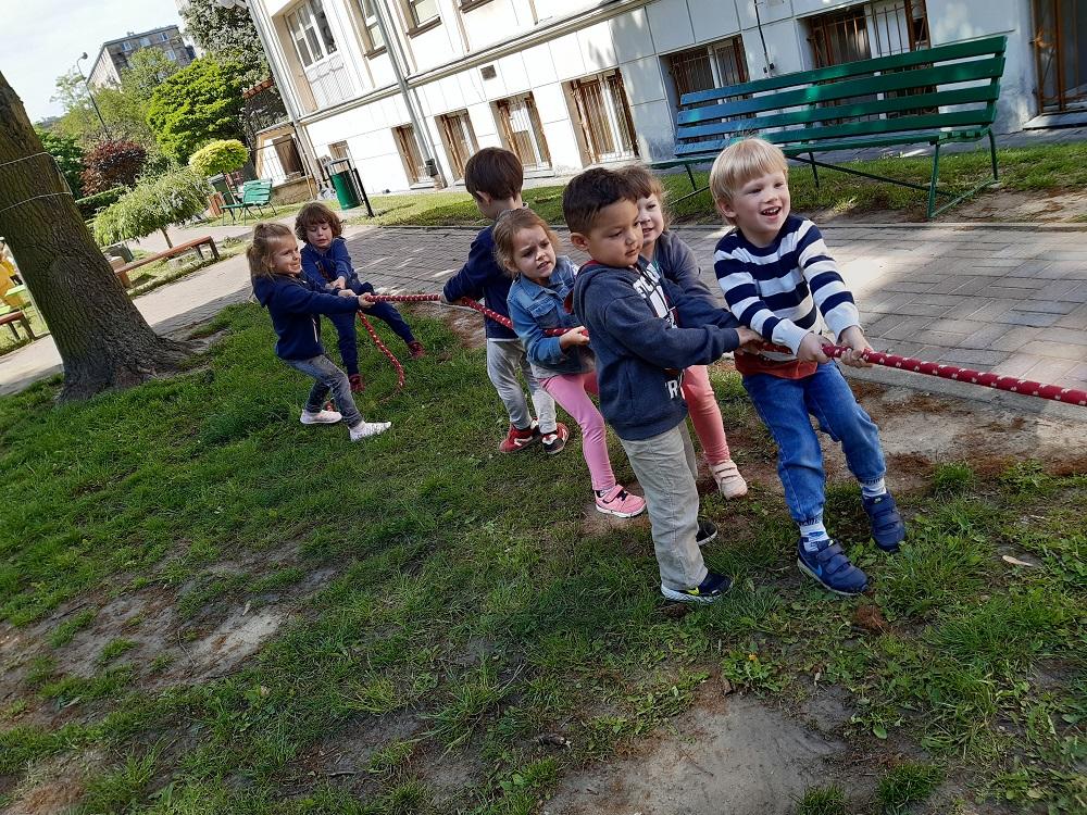 roześmiane dzieci ciągną linę, konkurencja - przeciąganie liny