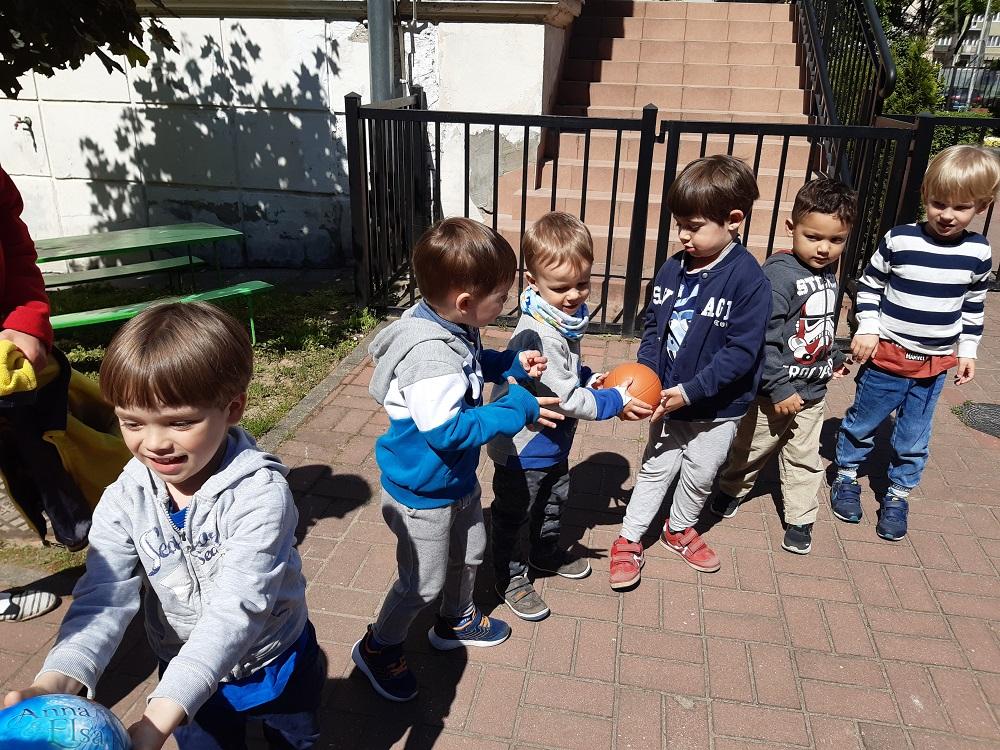"""zabawa """"Piłka parzy"""" - dzieci podają sobie piłki zrąk dorąk"""