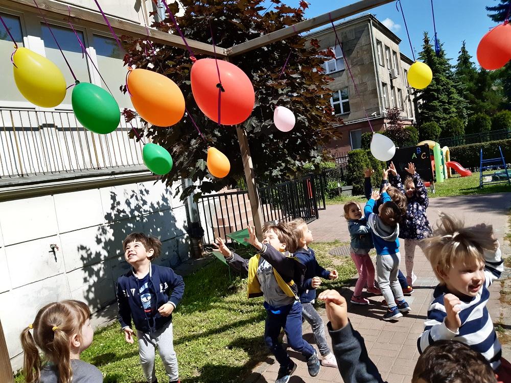 dzieci podskakują dozawieszonych nanitkach balonów
