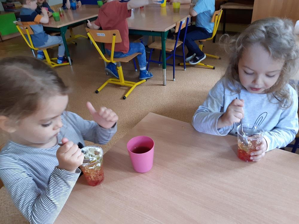 dzieci zapetytem jedzą deser - galaretkę zbitą śmietaną