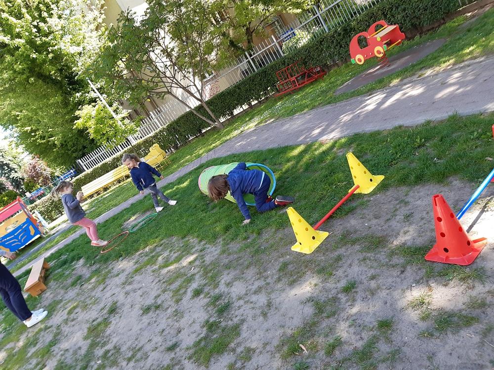 dzieci pokonują przeszkody ustawione natrawie - płotki, tunel.