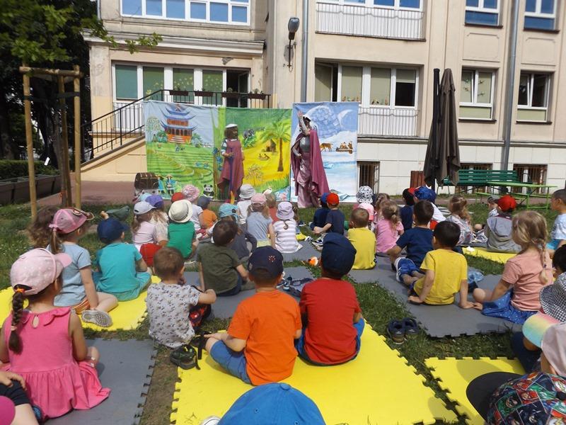 dzieci oglądaja przedstawienie teatralne wogrodzie